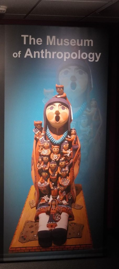 A figurine with many other figurines on it. The words The Museum of Anthropology written across the top.