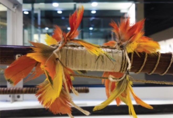 A bow wrapped in string with feathers wrapped around it.