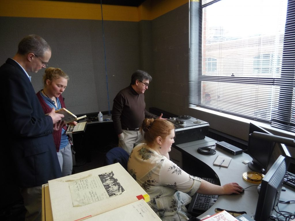 Four people working. Two reading a book, one on a computer, and another at a reel to reel machine.