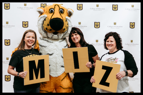 """SISLT Student Services (Ms. Megan Wilkinson, left; Ms. Amy Adam, right) and SISLT Director Dr. Rose Marra pal around with Truman! From left to right photo depicts Megan Wilkinson, Mascot Truman the Tiger, Rose Marra, and Amy Adam. Wilkinson is holding a placard with the letter """"M,"""" Marra is holding the letter """"I,"""" and Adam is holding the letter """"Z."""""""